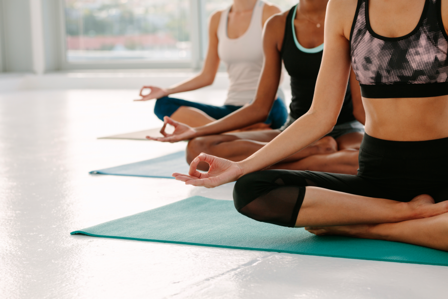 Females in gym class sitting on exercise mat with legs crossed and hands on knees. People meditating in Padmasana yoga pose at class. Cropped shot with focus on hands. Bild: de.stockadobe.com/Jacob Lund